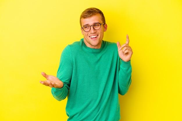 Jeune homme caucasien isolé sur mur jaune joyeux rire beaucoup. concept de bonheur.