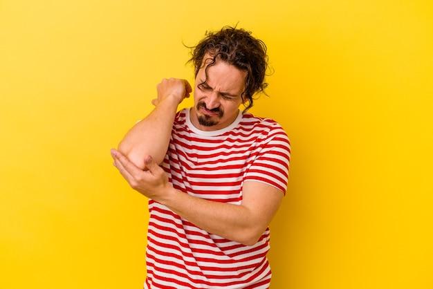 Jeune homme caucasien isolé sur mur jaune, massage du coude, souffrant après un mauvais mouvement