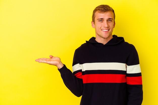 Jeune homme caucasien isolé sur un mur jaune montrant un espace de copie sur une paume et tenant une autre main sur la taille.