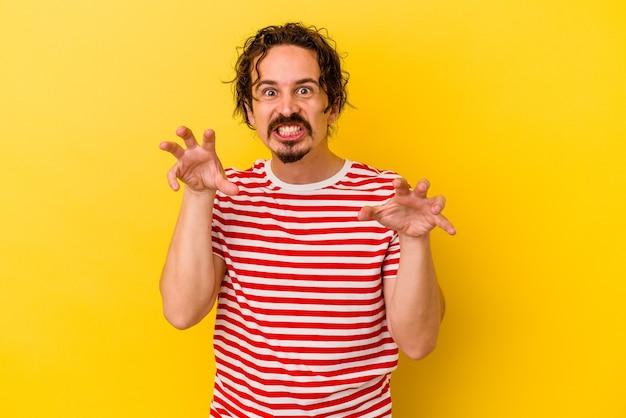 Jeune homme caucasien isolé sur un mur jaune montrant des griffes imitant un chat, geste agressif.