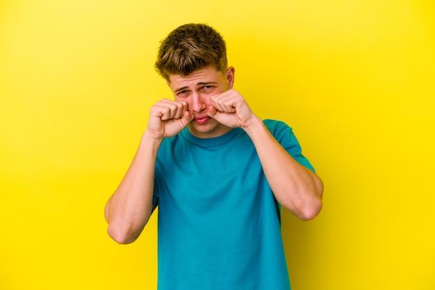 Jeune homme caucasien isolé sur mur jaune pleurnicher et pleurer de façon inconsolable