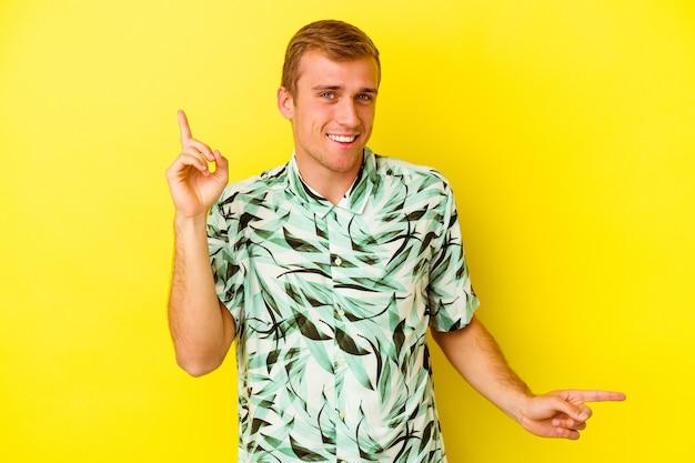 Jeune homme caucasien isolé sur un mur jaune pointant vers différents espaces de copie, en choisissant l'un d'entre eux, montrant avec le doigt.