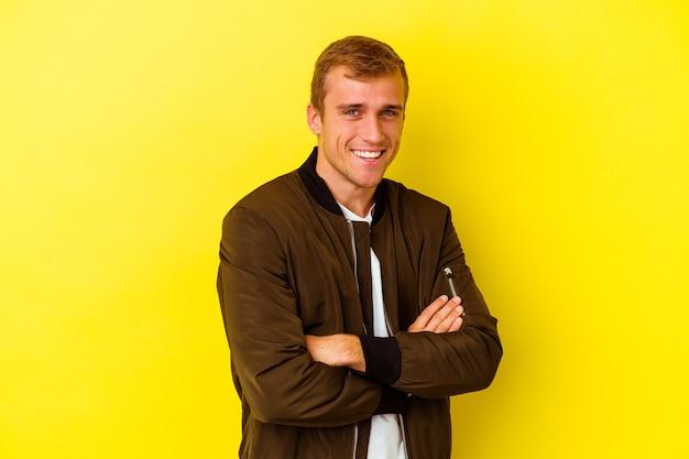 Jeune homme caucasien isolé sur un mur jaune en riant et en s'amusant.