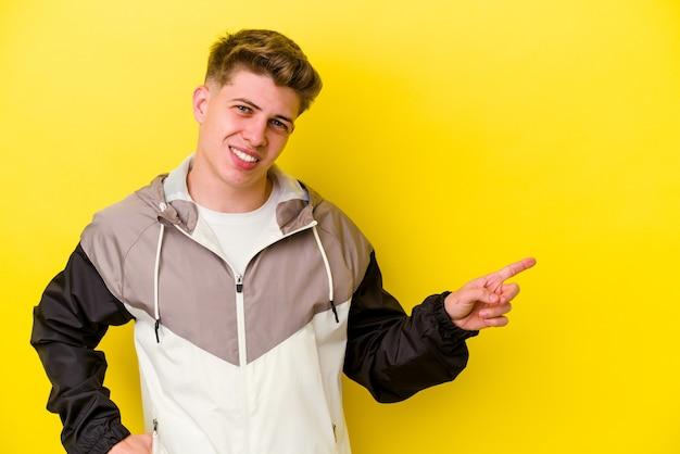 Jeune homme caucasien isolé sur mur jaune souriant joyeusement pointant avec l'index loin