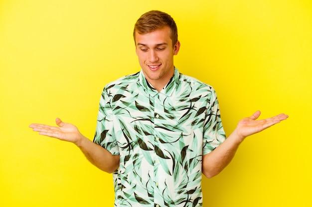 Jeune homme caucasien isolé sur un mur jaune tenant quelque chose avec des palmiers, offrant à la caméra.