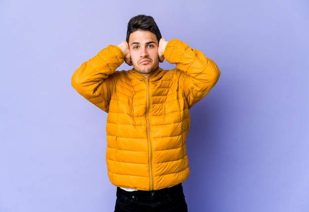 Jeune homme caucasien isolé sur un mur violet couvrant les oreilles avec les mains en essayant de ne pas entendre un son trop fort.