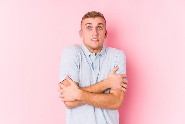 Jeune homme caucasien isolé qui devient froid en raison d'une basse température ou d'une maladie.