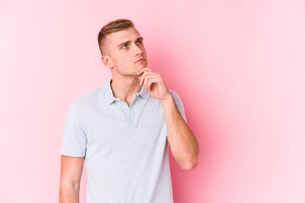Jeune homme caucasien isolé à la recherche sur le côté avec une expression douteuse et sceptique.