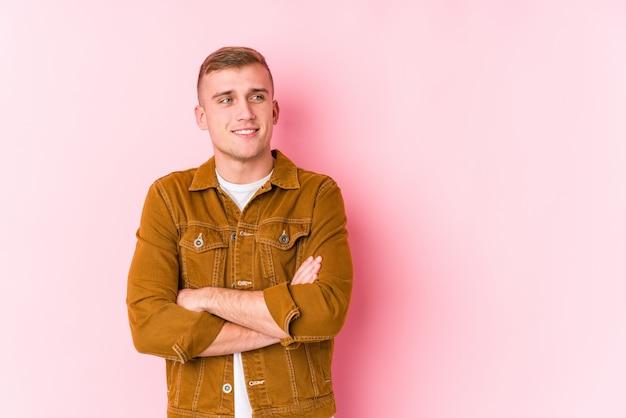 Jeune homme caucasien isolé souriant confiant avec les bras croisés.