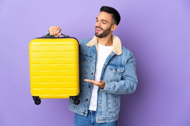 Jeune homme caucasien isolé en vacances avec valise de voyage