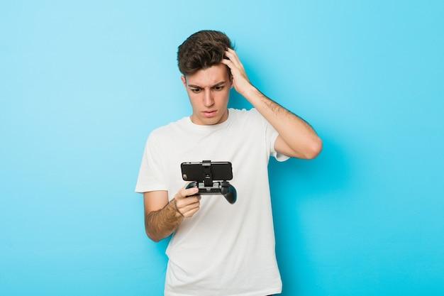 Jeune homme caucasien jouant à des jeux vidéo avec un téléphone choqué, elle s'est souvenue d'une réunion importante.