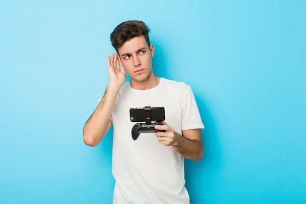 Jeune homme caucasien, jouer à des jeux vidéo avec téléphone en essayant d'écouter un potin.