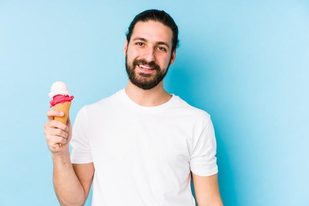 Jeune homme caucasien, manger une glace isolée heureux, souriant et joyeux.