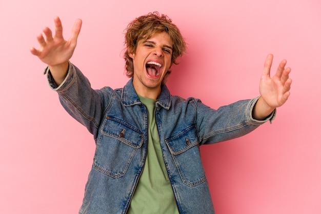 Jeune homme caucasien avec maquillage isolé sur fond rose se sent confiant en donnant un câlin à la caméra.