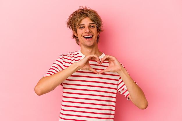 Jeune homme caucasien avec maquillage isolé sur fond rose souriant et montrant une forme de coeur avec les mains.