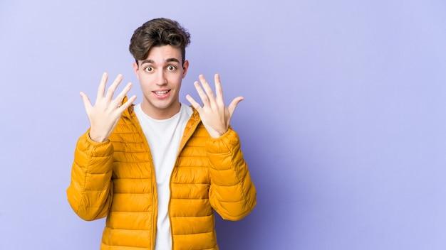 Jeune homme caucasien montrant le numéro dix avec les mains.