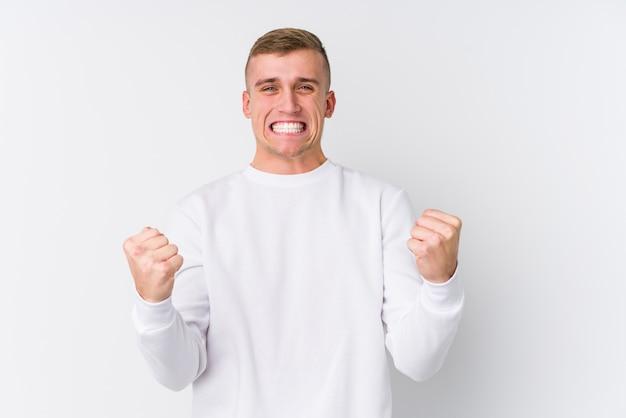 Jeune homme caucasien sur mur blanc applaudissant sans soucis et excité. concept de victoire.