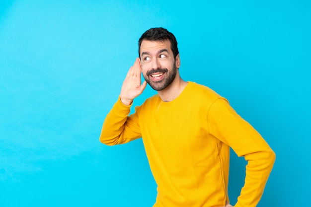 Jeune homme caucasien sur mur bleu isolé écouter quelque chose en mettant la main sur l'oreille