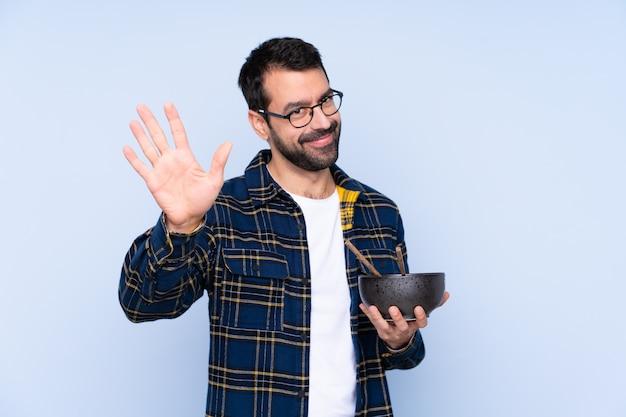 Jeune homme caucasien sur mur bleu saluant avec la main avec une expression heureuse tout en tenant un bol de nouilles avec des baguettes