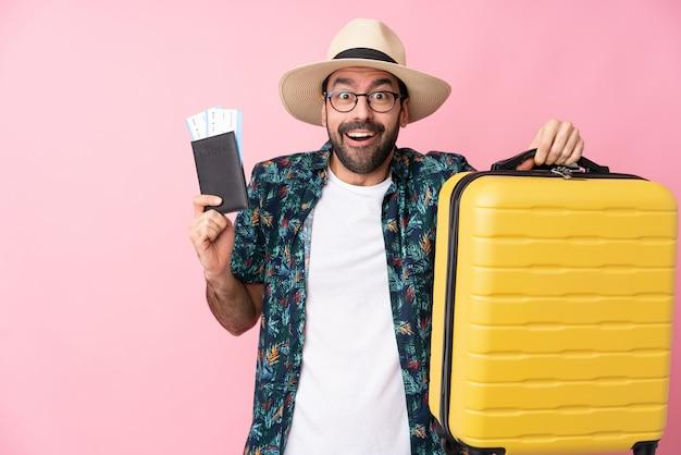Jeune homme caucasien sur mur isolé en vacances avec valise et passeport et surpris