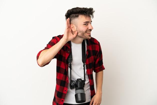 Jeune homme caucasien de photographe isolé sur fond blanc écoutant quelque chose en mettant la main sur l'oreille