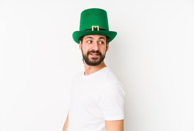 Jeune homme caucasien portant un chapeau de saint patrick isolé regarde de côté souriant, joyeux et agréable.