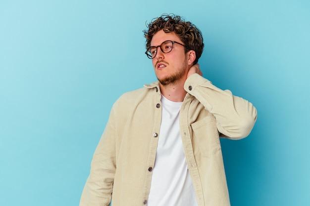 Jeune homme caucasien portant des lunettes isolé sur fond bleu ayant une douleur au cou due au stress, en le massant et en le touchant avec la main.