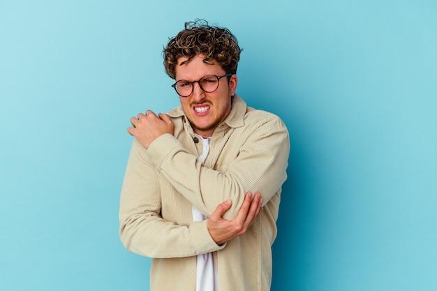 Jeune homme caucasien portant des lunettes isolé sur fond bleu massant le coude, souffrant après un mauvais mouvement.