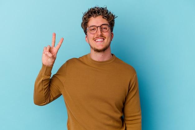 Jeune homme caucasien portant des lunettes isolé sur fond bleu montrant le signe de la victoire et souriant largement.