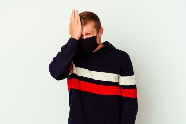 Jeune homme caucasien portant un masque contre le virus isolé sur un mur blanc en oubliant quelque chose, en frappant le front avec la paume et en fermant les yeux.