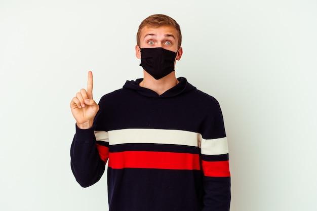 Jeune homme caucasien portant un masque pour virus isolé sur un mur blanc ayant une excellente idée, concept de créativité.