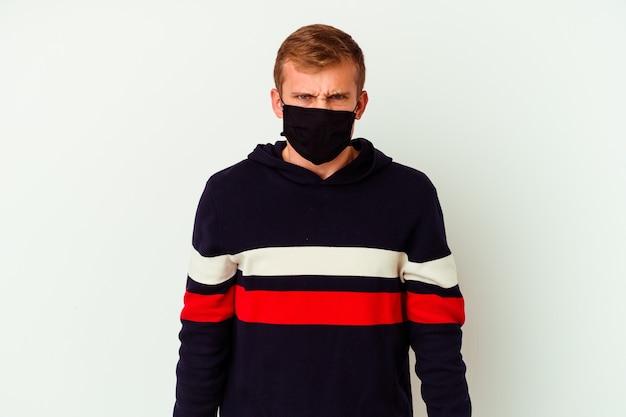 Jeune homme caucasien portant un masque pour virus isolé sur un mur blanc criant très en colère et agressif.