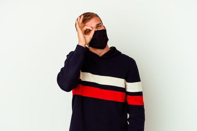 Jeune homme caucasien portant un masque pour virus isolé sur un mur blanc excité en gardant le geste ok sur les yeux.