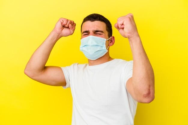 Jeune homme caucasien portant une protection contre le coronavirus isolé sur un mur jaune célébrant une journée spéciale, saute et lève les bras avec énergie.