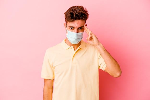 Jeune homme caucasien portant une protection contre le coronavirus isolé sur un mur rose pointant le temple avec le doigt, pensant, concentré sur une tâche
