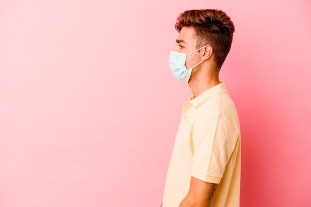 Jeune homme caucasien portant une protection contre le coronavirus isolé sur un mur rose regardant à gauche, pose sur le côté.