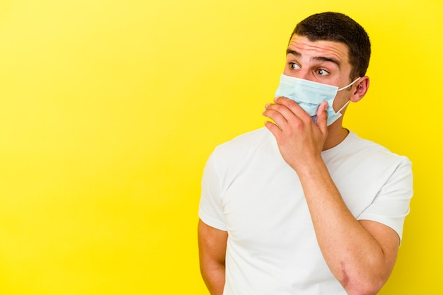 Jeune homme caucasien portant une protection contre le coronavirus sur jaune réfléchi à la recherche d'un espace de copie couvrant la bouche avec la main.