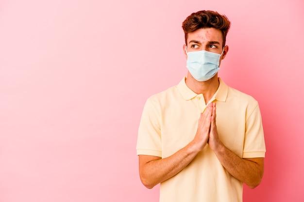 Jeune homme caucasien portant une protection contre le coronavirus sur le plan de composition rose à l'esprit, mettant en place une idée.