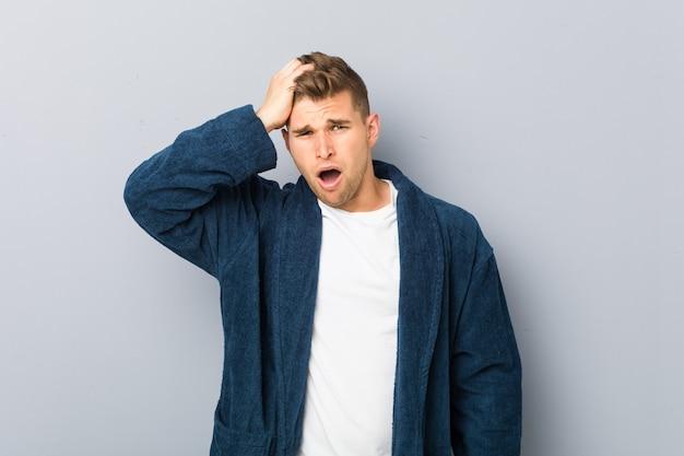 Jeune homme caucasien portant pyjama fatigué et très endormi en gardant la main sur la tête.