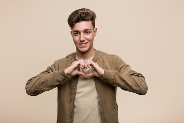 Jeune homme caucasien portant une veste marron souriant et montrant une forme de coeur avec ses mains.