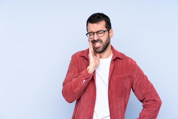 Jeune homme caucasien portant une veste en velours côtelé sur un mur bleu avec des maux de dents