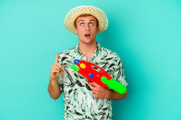 Jeune homme caucasien portant des vêtements d'été et tenant un pistolet à eau isolé sur blanc pointant vers le haut avec la bouche ouverte.