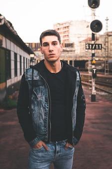 Jeune homme caucasien posant dans une gare