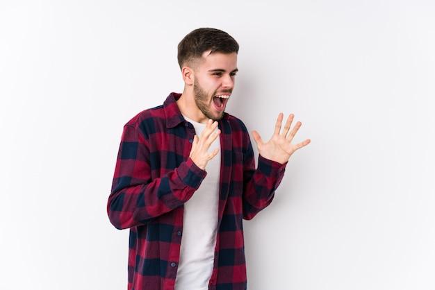 Jeune homme caucasien posant dans un mur blanc isolé crie fort, garde les yeux ouverts et les mains tendues.