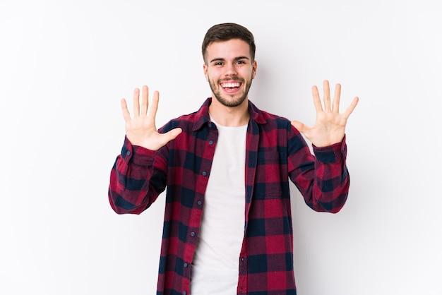 Jeune homme caucasien posant dans un mur blanc isolé montrant le numéro dix avec les mains.