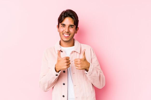 Jeune homme caucasien posant dans un mur rose isolé levant les deux pouces vers le haut, souriant et confiant.
