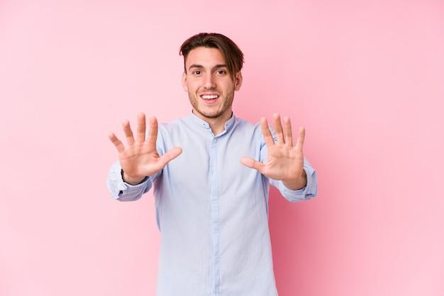 Jeune homme caucasien posant dans un mur rose isolé montrant le numéro dix avec les mains.