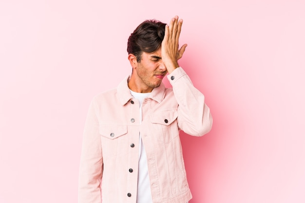 Jeune homme caucasien posant dans un mur rose isolé oubliant quelque chose, giflant le front avec la paume et fermant les yeux.