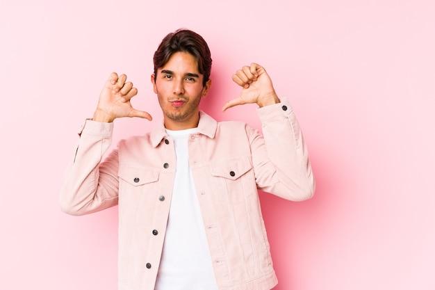Jeune homme caucasien posant dans un mur rose isolé se sent fier et confiant, exemple à suivre.