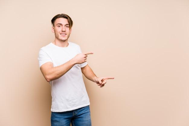 Jeune homme caucasien posant excité pointant avec les index loin.